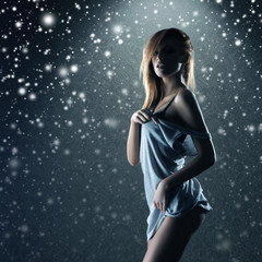 Young and sexy redhead woman on a snowy background