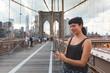 Young Woman Using Smart Phone on Brooklyn Bridge