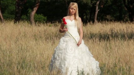 Blonde bride with poppy flower goes towards the camera in field
