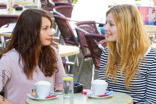 canvas print picture Zwei junge Frauen im Cafe sprechen miteinander