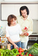 Happy woman and man  adding spices to the pot and in home kitche