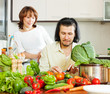 happy couple cutting vegetables in  kitchen