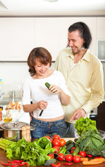 Happy couple with fresh vegetables in home kitchen