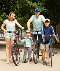 Family of four with bicycles and scooter in vacation