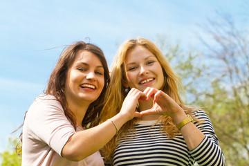 Zwei junge Frauen machen ein Fingerherz