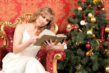 woman with book near the Christmas tree