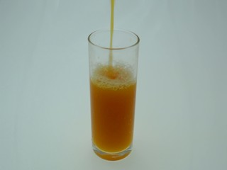Orange juice pouring into a glass