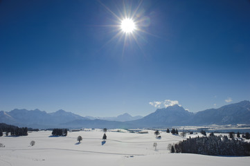sun and snow in winter at alps mountains in Bavaria