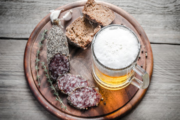 Slices of french Saucisson sausage with glass of beer
