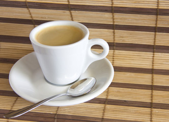 Espresso cup of coffee on straw placemat background