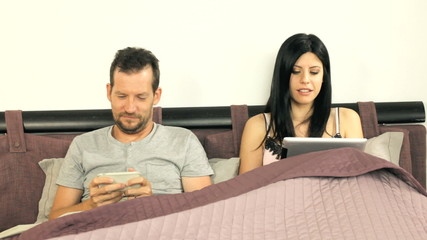 Couple playing in bed with tablet and smart phone