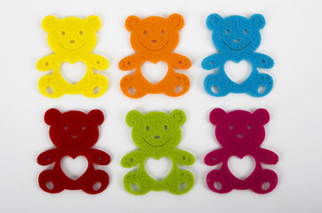 Six colorful teddy bear decorations over white background