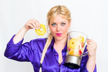 Blonde Frau mit Mixer voller Obst