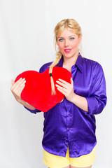 Blonde Frau mit Herz in der Hand