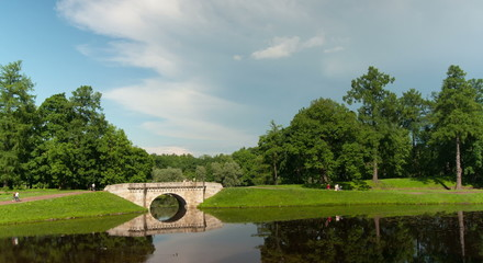 A bridge over a river in the park with clouds. Time lapse.