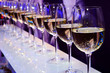 Nightclub glasses with white wine lit by festive lights