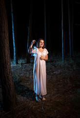 young woman in nightgown in forest at night with gas lamp