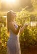 beautiful smiling woman catching water drops at garden