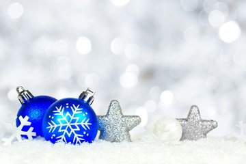 Blue and silver Christmas ornaments with twinkling background