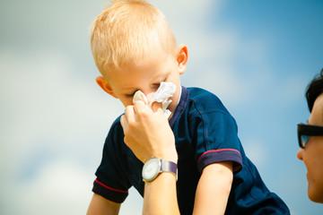 Child blowing nose. Boy with tissue. Catarrh or allergy
