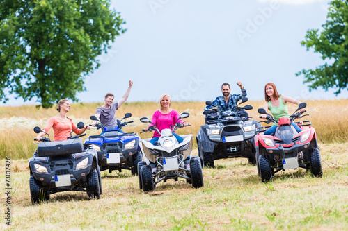 Friends driving off-road with quad bike or ATV - 73017426