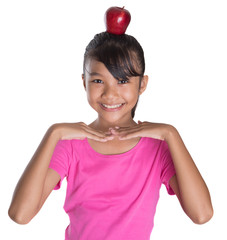 Young Asian Malay girl balancing a red apple on her head