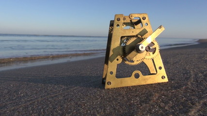 Time and ocean concept. Clock brass gear on sand