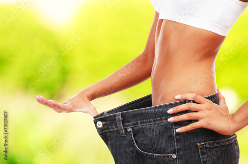 canvas print picture Beautiful young woman with big jeans on bright background