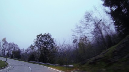 Car drives on mountain road above cloud POV