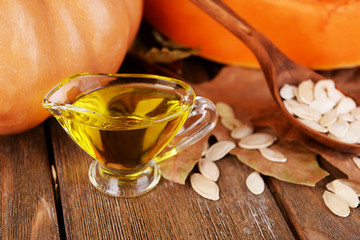 Pumpkin seed oil in glass sauce-boat on wooden background