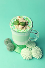 Mint milk dessert with nuts in glass on color background