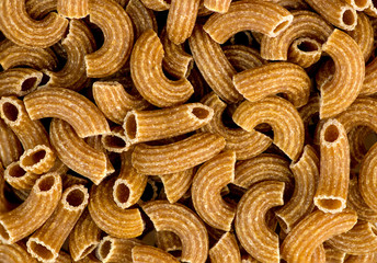 Macro background texture of wholemeal ribbed uncooked raw macaro