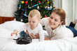 Young mother and toddler son playing with RC controller