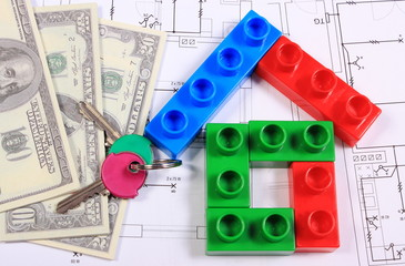 House of colorful building blocks, keys and banknotes on drawing