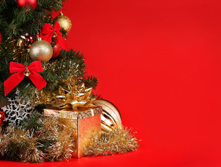 Christmas. Gift Box under Christmas Tree over Red Background