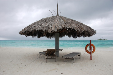 Beach umbrella and sun lounger with lifebuoy at Maldives