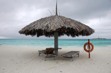 Beach umbrella and sun lounger with lifebuoy at Maldives