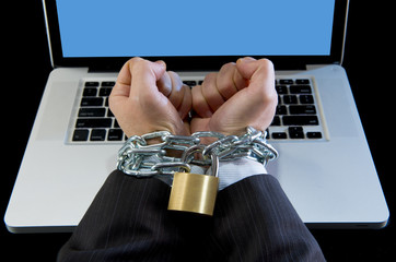 businessman addicted to work chain locked to computer laptop
