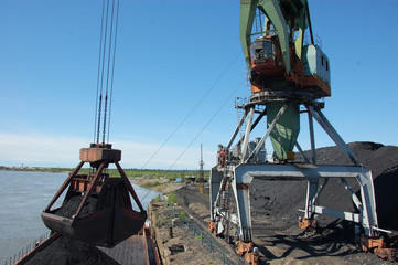 Crane loading coal to ship at Kolyma river port