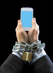 businessman addicted to work chain locked to mobile phone