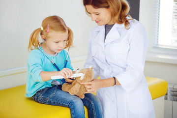 Pediatrician doctor examining little girl.