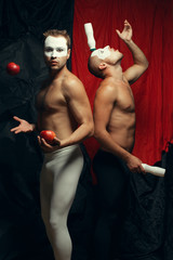 Freak circus concept. Two muscular mime artists, clowns juggling
