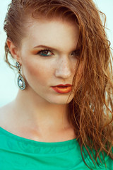 Fashion portrait of young model with wet long ginger (red) hair