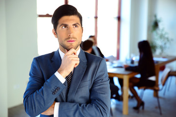 Pensive businessman standing in front of colleagues