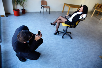 Businessman taking businesswoman's photo on smartphone in office