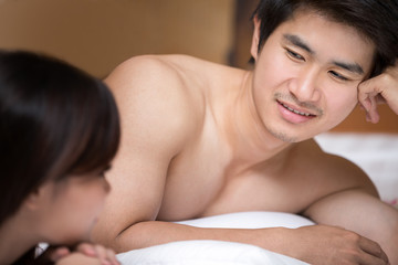 A happy young couple lying on the bed