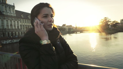 Young woman talking on mobile phone in the city, slow motion.