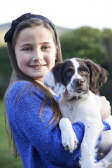 Girl Holding Pet Spaniel Puppy Outdoors In Garden