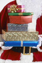Close Up Of Santa Claus Holding Pile Of Gift Wrapped Presents