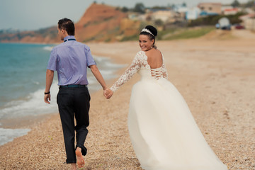Wedding couple, bride and groom, walking on a beautiful beach